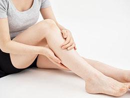 右足のふくらはぎを触る女性
